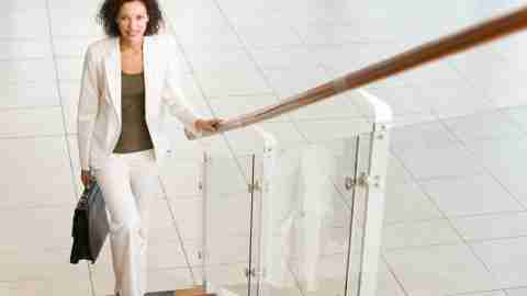 """A businesswoman stands at the bottom of a flight of stairs wondering, """"Should I tell my boss I have ADD?"""""""