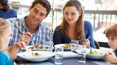 A family eats a meal of ADHD recipes, like high-protein salads, together at a cafe