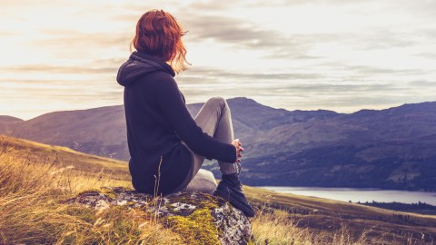 Woman watching the sunset, consumed by negative thoughts she should challenge.