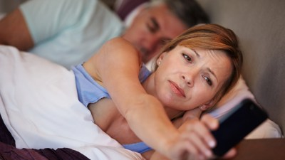 A woman who can't sleep setting a bed time alarm.