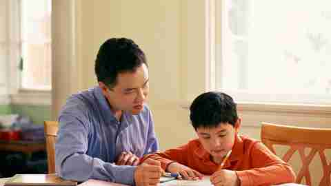 A father helps his child, who has ADHD, with his homework assignment
