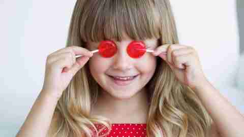 A young girl, with ADHD, has lollipops over her eyes