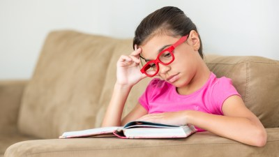 An angry child with ADHD reads a book about how to manage emotions.