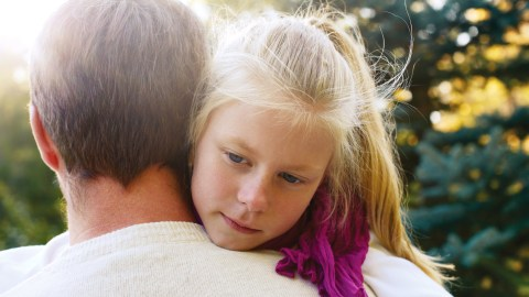 A father gives his angry child with ADHD a hug, one way to help manage difficult emotions.