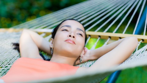 Woman overcoming analysis paralysis by laying in a hammock