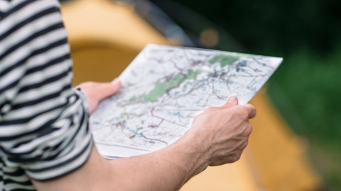A person with analysis paralysis trying to read a map