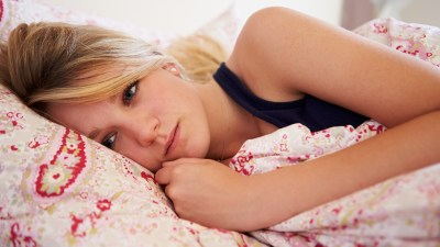 A teen girl is in bed, depressed, which requires a different ADHD treatment strategy.