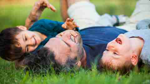 A dad with ADHD plays with his sons with ADHD in the grass.