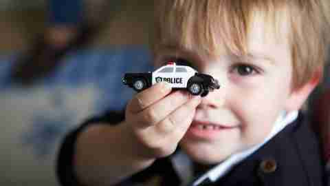 A boy with ADHD holds a toy police car.