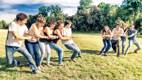 An ADHD support group plays tug of war in a field.
