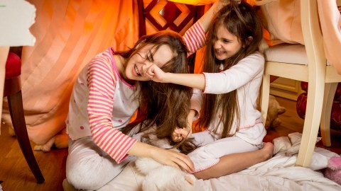 A girl with ADHD pinches her friend in a play fort.