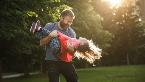 A dad plays outside with his daughter with ADHD to expend extra energy and avoid a meltdown.
