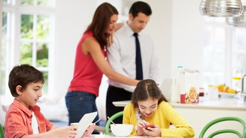 Children with ADHD hyperfocus on their phones and computer at the kitchen table with Mom and Dad in the background.