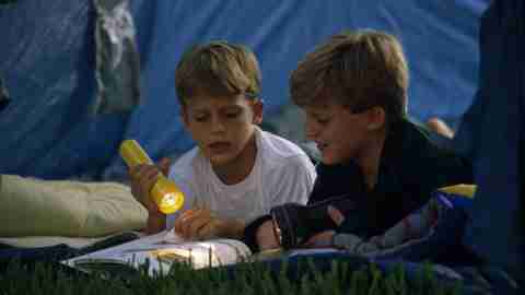 Two boys reading in a tent at an ADHD summer camp