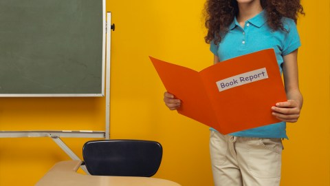 A female student presenting a book report on learning loss during summer school