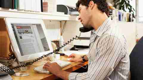 A man with ADHD is putting things off by talking on the phone at his desk.