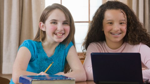 Two students work on homework together in a well organized and clutter free environment, a good school organization idea.