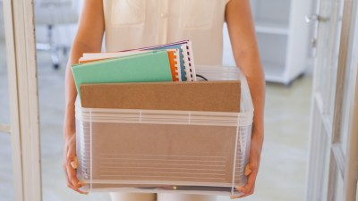 Woman with ADHD carrying box of things out of office after being fired