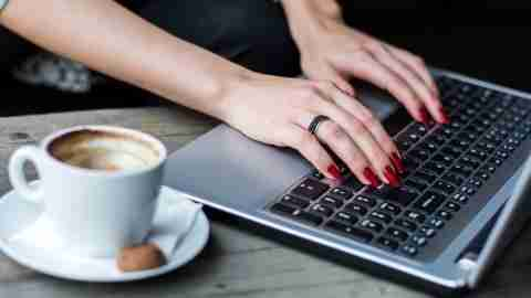 Hands of woman typing on laptop for her ADHD blog with cappuccino next to her