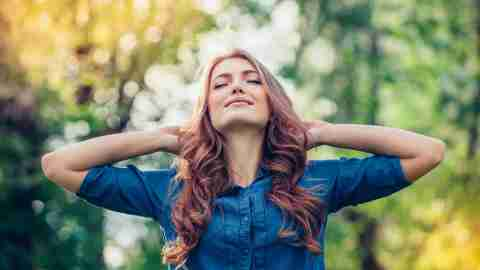 Woman with ADHD standing outside with hands behind head and eyes closed relived to be stress-free