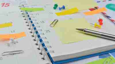 A planner covered with sticky notes, one of our suggested ADHD organization tools