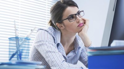"A young woman with ADHD, sitting in front of a computer and thinking ""I am so bored at work!"""