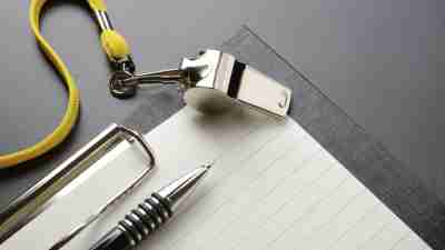 A pen and paper next to a whistle that might be used by an ADHD life coach