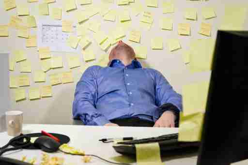 A tired man at work can't stop procrastinating due to his adult ADHD.