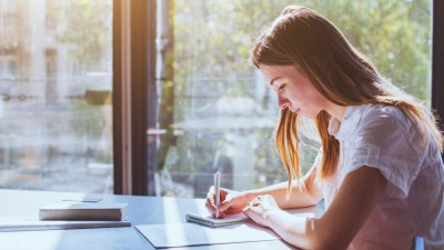 Profile of college student with ADHD taking notes seated by window