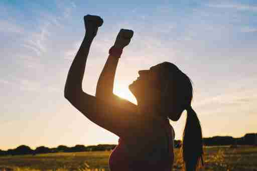 Woman with ADHD celebrating her accomplishment with arms raised
