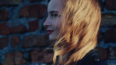 Profile of woman staring ahead smiling with wind blowing hair forward coming to terms with her adult ADHD