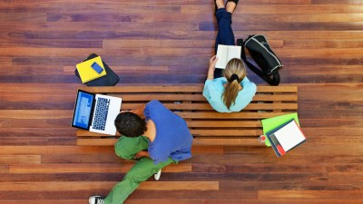 Bird's eye view of two students with ADHD studying on bench