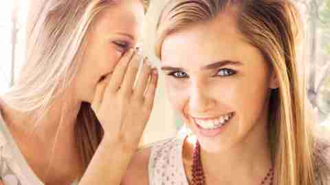 Teen girl with ADHD whispering something in ear of friend who is laughing