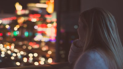 Girl with ADHD and depression stares out from apartment onto city street at night