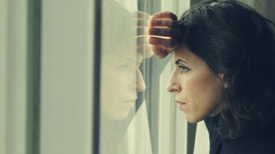 Woman with ADHD staring out of window in pain from menstruation cycle