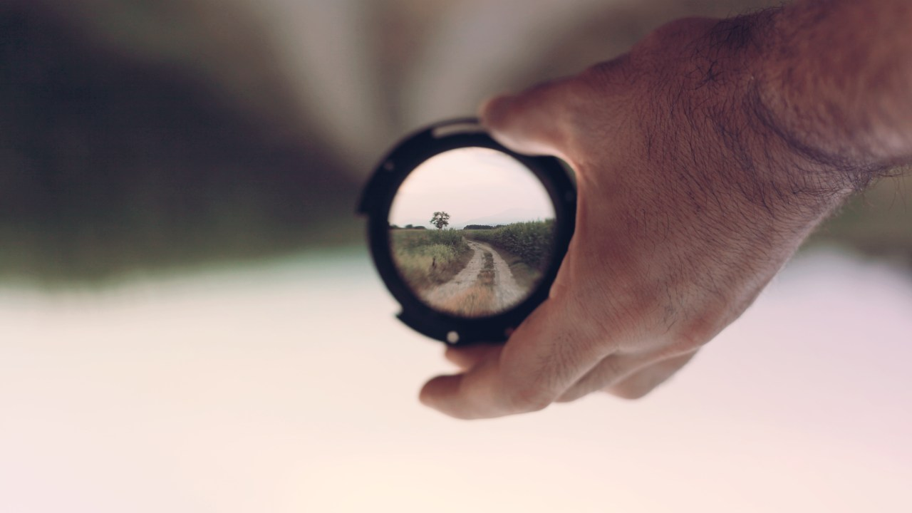 Hyperfocus: Man with ADHD holding lens with focused image of landscape inside it