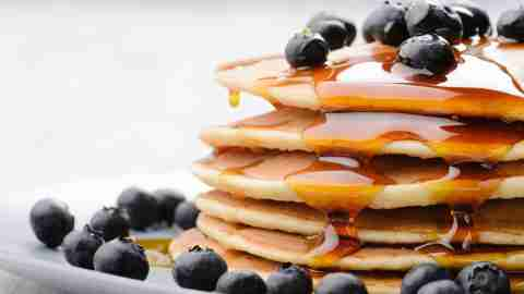 Stack of pancakes covered in maple syrup with blueberries makes a good breakfast for ADHD kids