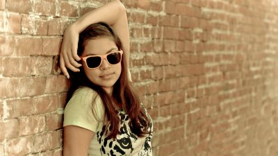 Preteen girl with ADHD leans against brick wall