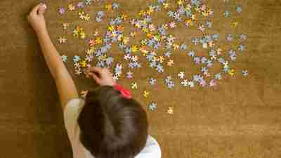 A kid playing with a puzzle to avoid a meltdown after school