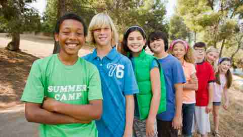 Kids at ADHD summer camp smiling and standing in line out doors