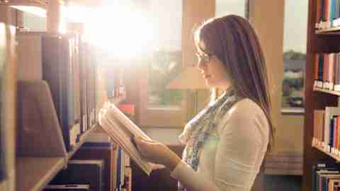 Teen girl with ADHD in library reading books and preparing for college