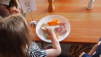 Little girl with ADHD eating plate of food at diner