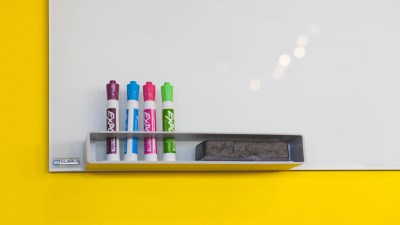 A whiteboard with markers to help children manage time and not be late for school