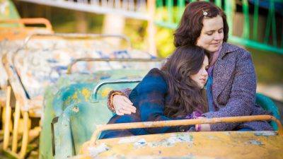 A mom and daughter hugging on a roller coaster, overcoming parenting-related guilt that can come with ADHD
