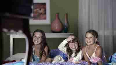 Three little girls with ADHD watching TV during a slumber party.