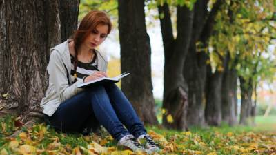 A teenager with ADHD sits under trees taking notes