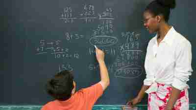 Student with ADHD writing out math problem on blackboard with teacher looking on