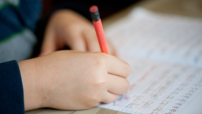 Hands of student with ADHD writing and practicing penmanship in notebook