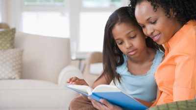 Mother helping her daughter with ADHD work on reading comprehension in their living room