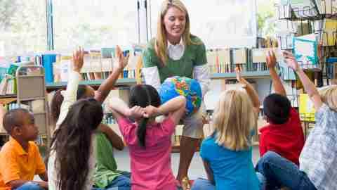 Children with ADHD at school sitting around teacher.